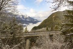 Viaduct through alpine scenery. Viaduct passing through the treetops in snowy winter alpine scenery with low lying clouds in the valley between mountain peaks stock image