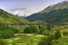 Viaduct leading across a green valley with a mountain ridge in the background royalty free stock images