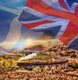 Viaducto ferroviario de Glenfinnan en Escocia con el tren del vapor de Jacobite contra banderas escocesas del ANG británicos imagen de archivo libre de regalías