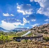 Viaducto ferroviario de Glenfinnan en Escocia con el tren del vapor de Jacobite contra puesta del sol foto de archivo libre de regalías