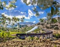 Viaducto ferroviario de Glenfinnan en Escocia con el tren del vapor de Jacobite contra puesta del sol sobre el lago Foto de archivo