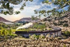Viaducto ferroviario de Glenfinnan en Escocia con el tren del vapor de Jacobite contra puesta del sol sobre el lago Foto de archivo libre de regalías