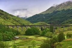 Viadukt, der über einem grünen Tal mit einem Gebirgsrücken im Hintergrund führt Lizenzfreie Stockbilder