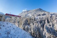 Viadukt Langwies in der Schweiz im Sonnenschein, Winter, Schnee, blau Stockbild