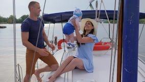 A viagem da família no loch no barco de prazer, viaja os pais novos com o rapaz pequeno no rio, feriado de pares felizes com bebê video estoque