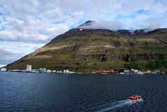 Viagem de Islândia Flutuador do barco no mar na paisagem da montanha em Sejdisfjordur, Islândia Costa de mar com a montanha no cé fotografia de stock