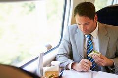 Viagem de trem de Eating Sandwich On do homem de negócios Fotografia de Stock Royalty Free