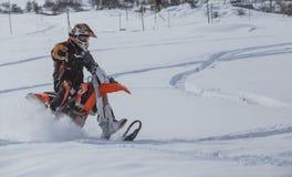Viagem do carro de neve do snowbike de Enduro com a bicicleta da sujeira alta nas montanhas Fotos de Stock Royalty Free