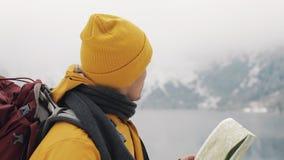 Viagem nas montanhas O caminhante novo usa um mapa de papel da área Procura o trajeto Aprecia a aventura e o curso Em video estoque