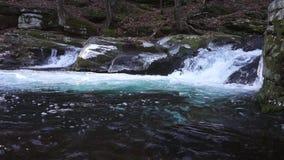 Viagens de jorro da cachoeira através das fissuras arredondadas da rocha video estoque