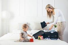 Viaggiando con i bambini La madre felice con il suo imballaggio del bambino copre per la festa Immagine Stock Libera da Diritti