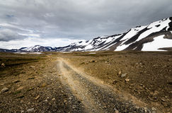 Viaggiando giù una strada della ghiaia in montagne nevose dell'Islanda fotografie stock libere da diritti