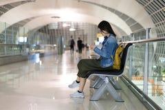 Viaggiatore asiatico della donna che per mezzo dello Smart Phone, imbarco aspettante al terminale dell'aeroporto Fotografia Stock