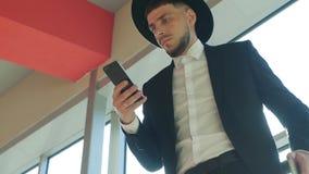 Viaggiatore caucasico dell'uomo in una condizione del cappello alla stazione e nell'esaminare il telefono, primo piano, movimento video d archivio