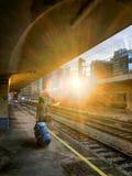 Viaggiatore che aspetta sulla piattaforma accanto alle rotaie vuote per iniziare la sua vacanza fotografia stock