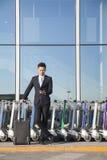 Viaggiatore che esamina cellulare accanto alla fila dei carretti dei bagagli Fotografie Stock