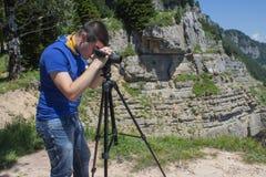 Viaggiatore che guarda la natura dall'alta montagna con portata di macchia, treppiede del binocolo immagini stock libere da diritti