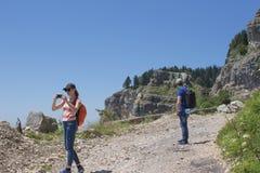 Viaggiatore che guarda la natura dall'alta montagna con portata di macchia, treppiede del binocolo Immagine Stock