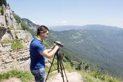 Viaggiatore che guarda la natura dall'alta montagna con portata di macchia, treppiede del binocolo fotografie stock libere da diritti