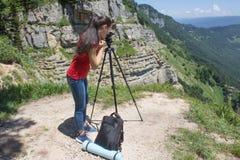 Viaggiatore che guarda la natura dall'alta montagna con portata di macchia, treppiede del binocolo immagini stock