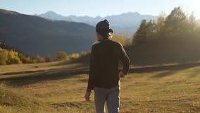 Viaggiatore che indica e che cammina in montagne di autunno di tramonto archivi video