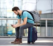 Viaggiatore che si siede inviando messaggio di testo Immagine Stock