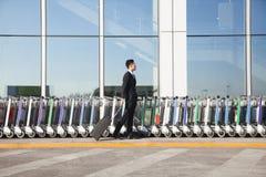 Viaggiatore con la valigia accanto alla fila dei carretti dei bagagli all'aeroporto Fotografia Stock