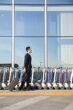 Viaggiatore con la valigia accanto alla fila dei carretti dei bagagli all'aeroporto Immagine Stock