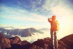 Viaggiatore con zaino e sacco a pelo asiatico della donna che prende foto con lo smartphone Fotografia Stock