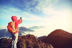 Viaggiatore con zaino e sacco a pelo asiatico della donna che prende foto con lo smartphone Fotografie Stock Libere da Diritti