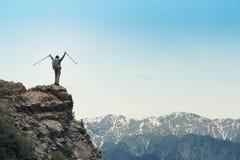 Viaggiatore con zaino e sacco a pelo a braccia aperte sulla scogliera del picco di montagna Immagine Stock