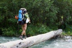 Viaggiatore con zaino e sacco a pelo che attraversa il fiume. Fotografia Stock Libera da Diritti
