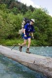 Viaggiatore con zaino e sacco a pelo che attraversa il fiume. Fotografia Stock
