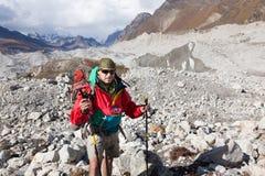 Viaggiatore con zaino e sacco a pelo che attraversa il ghiacciaio di Ngozumpa nel Nepal Fotografie Stock Libere da Diritti