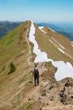Viaggiatore con zaino e sacco a pelo che cammina alla cresta della montagna del fellhorn nel allg Fotografie Stock