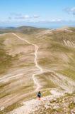 Viaggiatore con zaino e sacco a pelo che cammina nelle montagne Fotografia Stock Libera da Diritti
