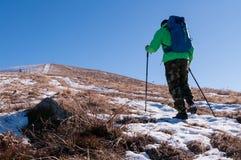 Viaggiatore con zaino e sacco a pelo che cammina sul picco di montagna Immagini Stock Libere da Diritti