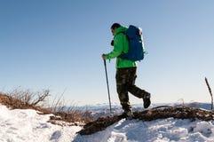 Viaggiatore con zaino e sacco a pelo che cammina sul picco di montagna Immagine Stock