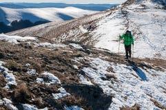 Viaggiatore con zaino e sacco a pelo che cammina sul picco di montagna Immagine Stock Libera da Diritti