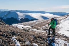 Viaggiatore con zaino e sacco a pelo che cammina sul picco di montagna Fotografia Stock Libera da Diritti