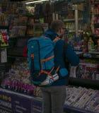Viaggiatore con zaino e sacco a pelo che compra una soda fotografia stock