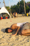Viaggiatore con zaino e sacco a pelo che dorme sulla spiaggia dopo il partito della luna piena, tailandese Immagini Stock