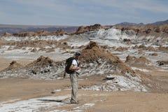 Viaggiatore con zaino e sacco a pelo che esplora la valle della luna nel deserto di Atacama, Cile Fotografia Stock