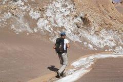 Viaggiatore con zaino e sacco a pelo che esplora la valle della luna nel deserto di Atacama, Cile Immagine Stock