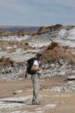 Viaggiatore con zaino e sacco a pelo che esplora la valle della luna nel deserto di Atacama, Cile Fotografie Stock