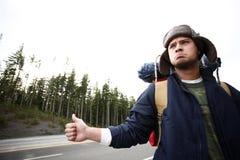 Viaggiatore con zaino e sacco a pelo che fa auto-stop fotografie stock