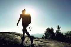 Viaggiatore con zaino e sacco a pelo che fa un'escursione sulla cima della montagna di alba Fotografia Stock