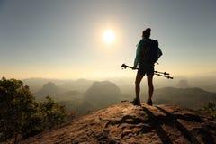 Viaggiatore con zaino e sacco a pelo che fa un'escursione sulla cima della montagna di alba Fotografie Stock Libere da Diritti