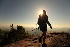 Viaggiatore con zaino e sacco a pelo che fa un'escursione sulla cima della montagna di alba Fotografia Stock Libera da Diritti