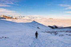 Viaggiatore con zaino e sacco a pelo che fa un'escursione sulla neve sulle alpi Retrovisione, stile di vita di inverno, sensibili Fotografia Stock